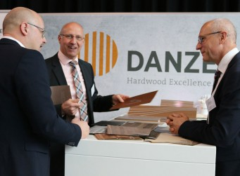 Danzer at the Future Interior Summit that focuses on future developments in automotive interiors: Danzer Vice President Sales Europe Ralf Bußmann (second from left) and Project Manager Thomas Wenk (right) talking to a visitor.