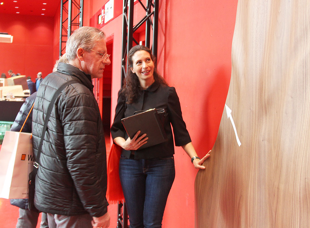 "Visitors at com:bau and Gertraud Storz, Danzer's Director Specification Sales in front of the Danzer ""Wonderwall"" – a wave-shaped, three-meter-high wall covered with Danzer 3D-Veneer Walnut."